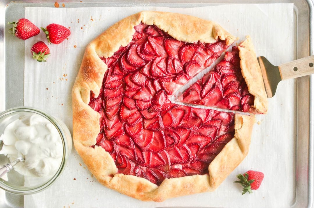a strawberry galette with fresh berries and whipped cream