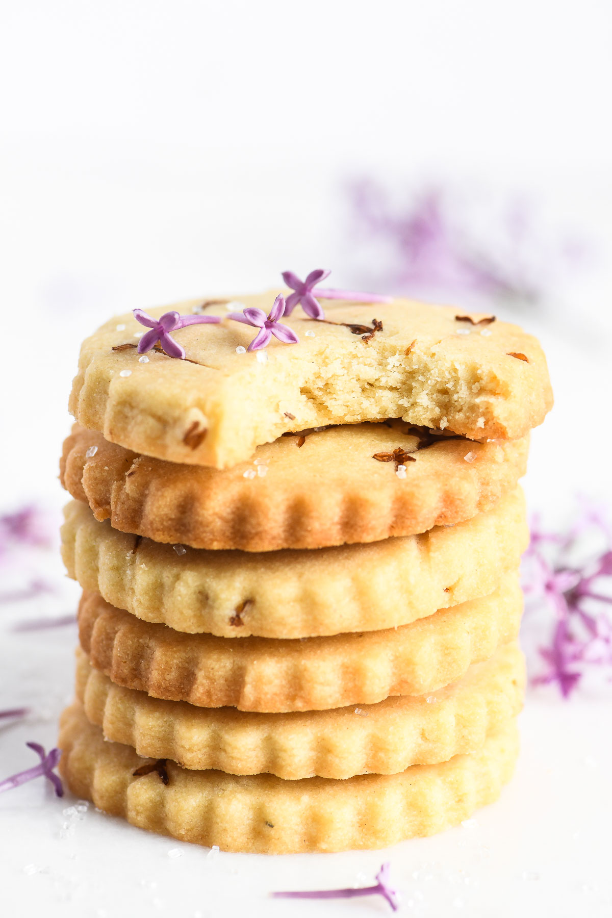a stack of lilac sugar shortbread cookies with lilac blossoms