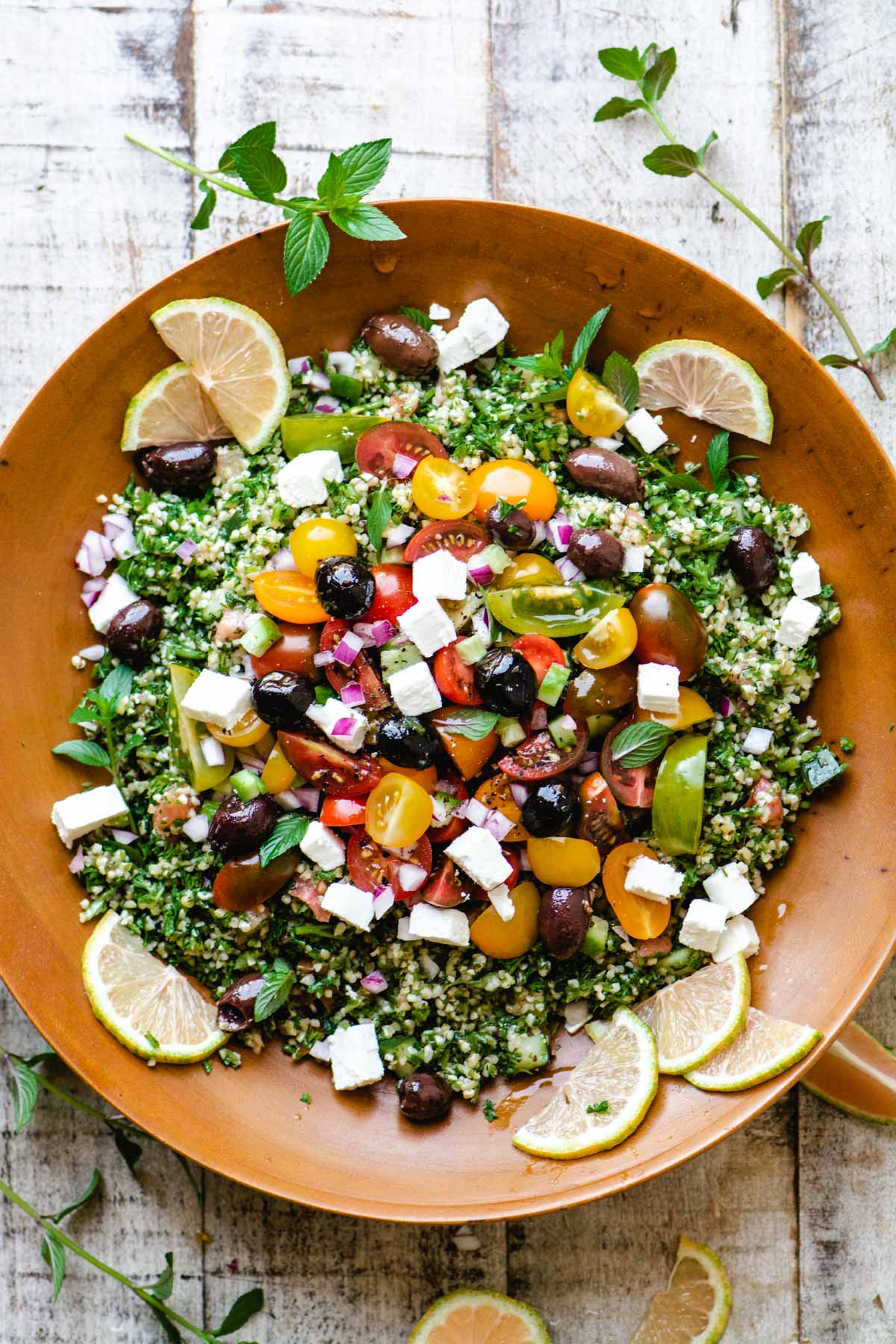 bowl of tabbouleh salad topped with tomatoes, olives, and feta cheese