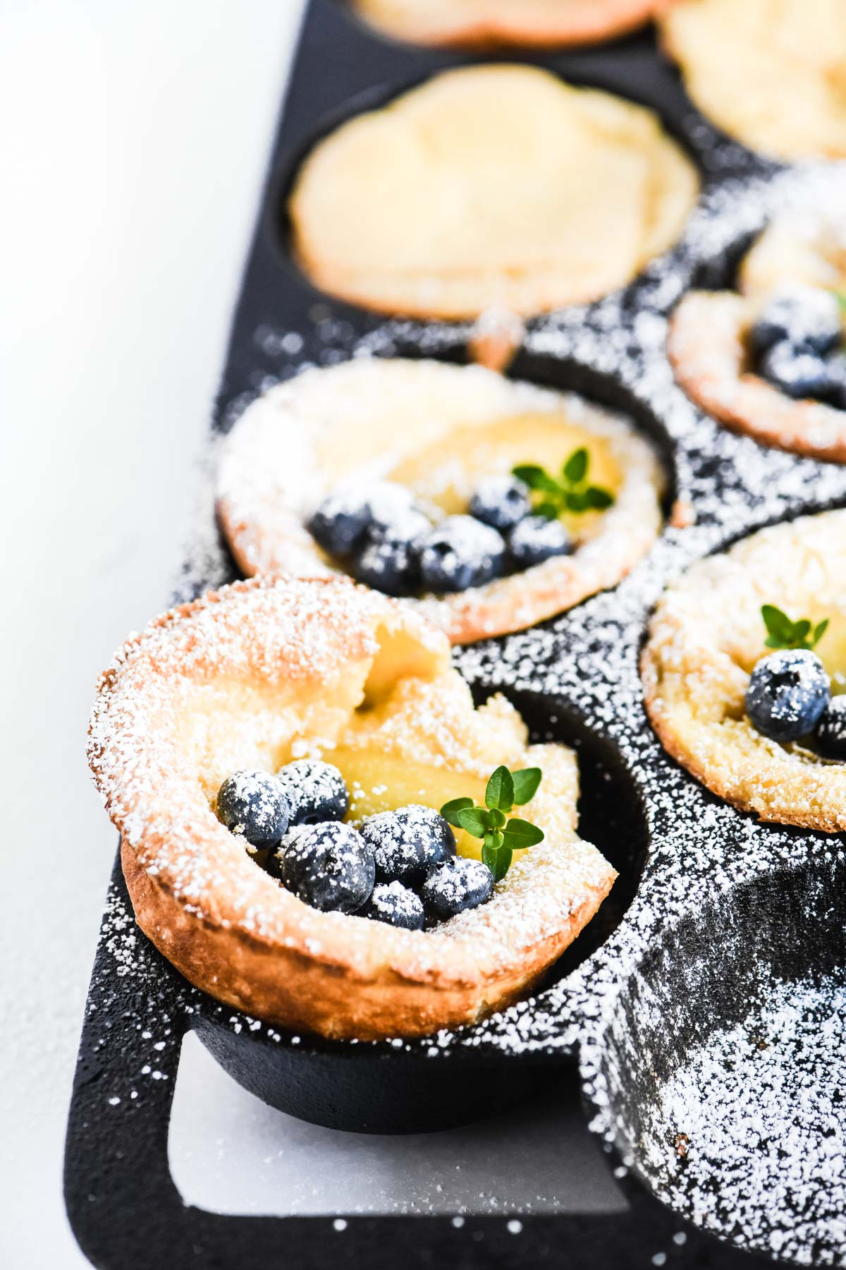 mini Dutch babies with lemon curd and blueberries in a cast iron pan