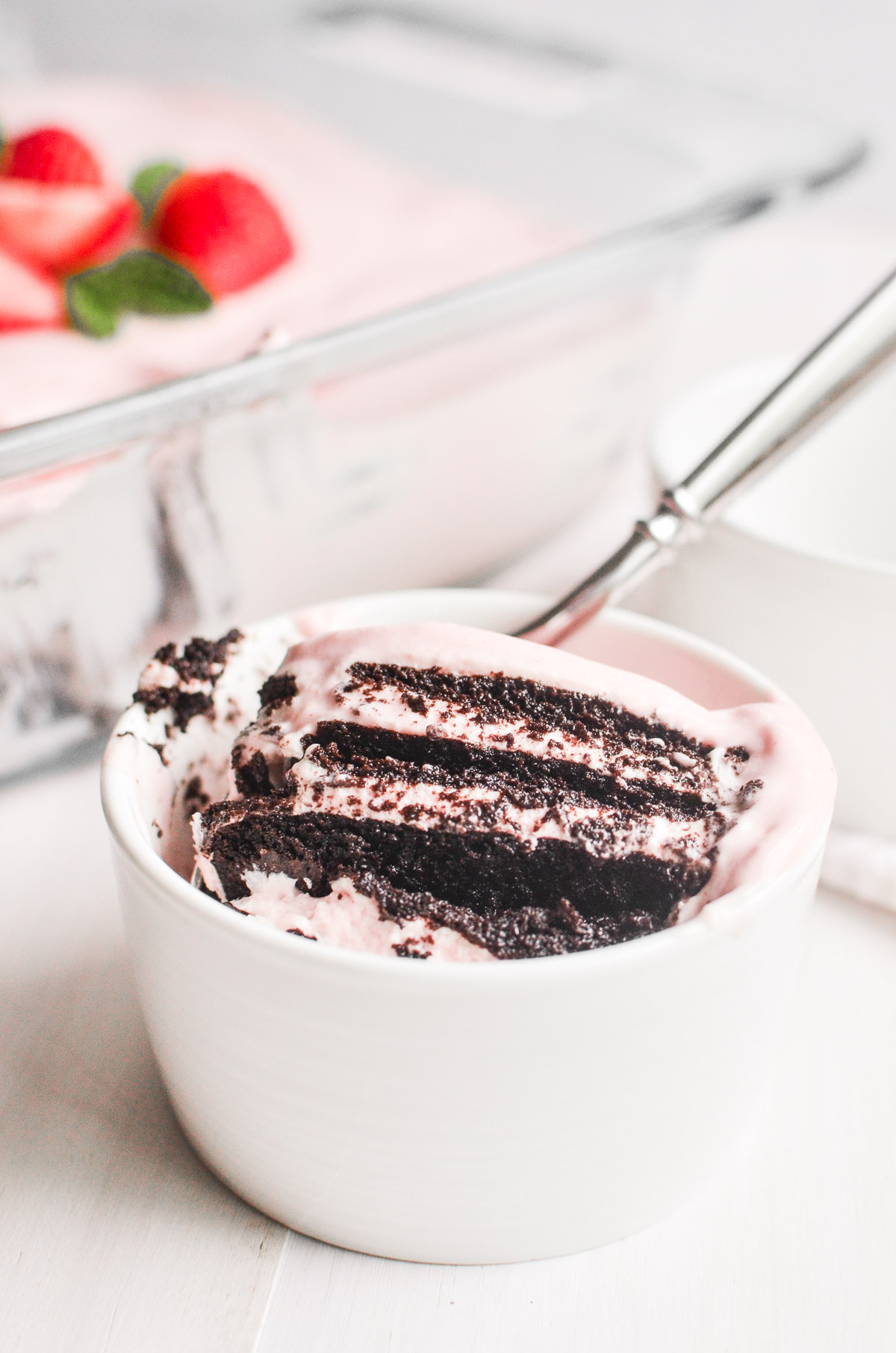 A serving of strawberry icebox cake in a white cup with a spoon.