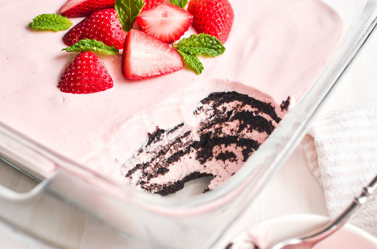 Strawberry icebox cake with a serving scooped out.