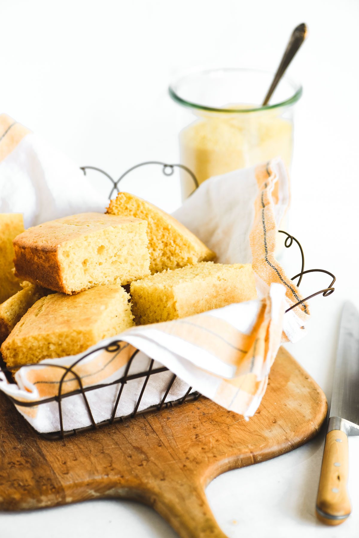 Cornbread in a basket on a wooden cutting board.