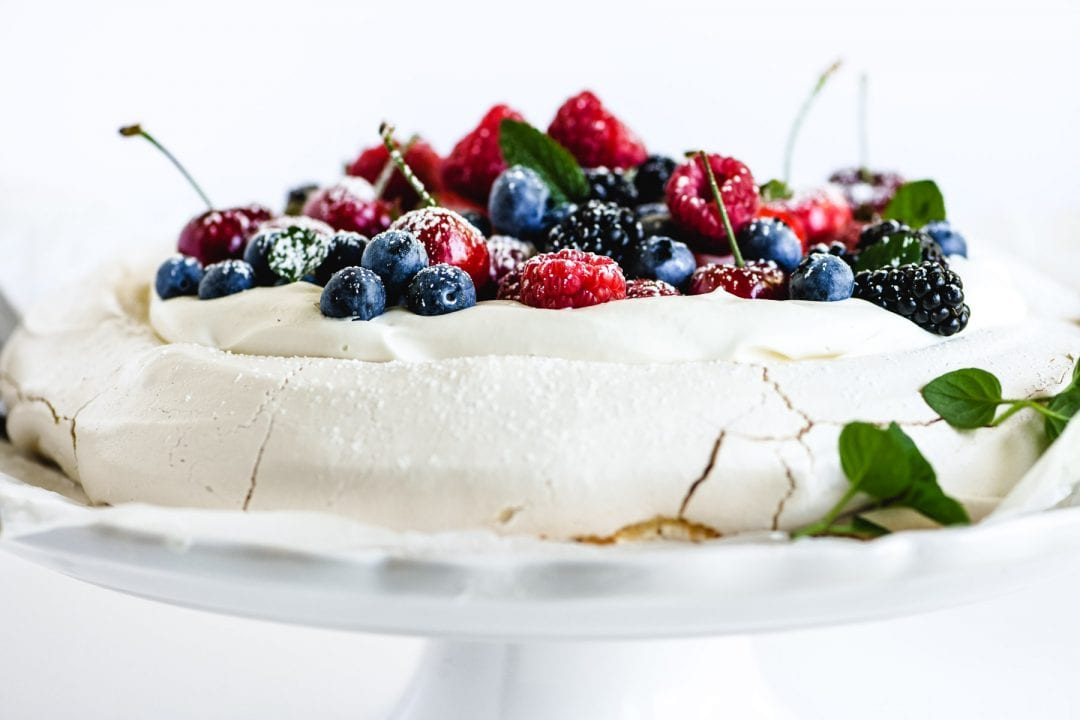 berry pavlova on a cake stand with fresh mint