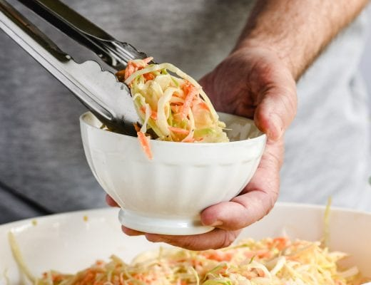 serving up buttermilk coleslaw with tongs