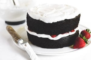 assembling a chocolate strawberry cake with whipped cream