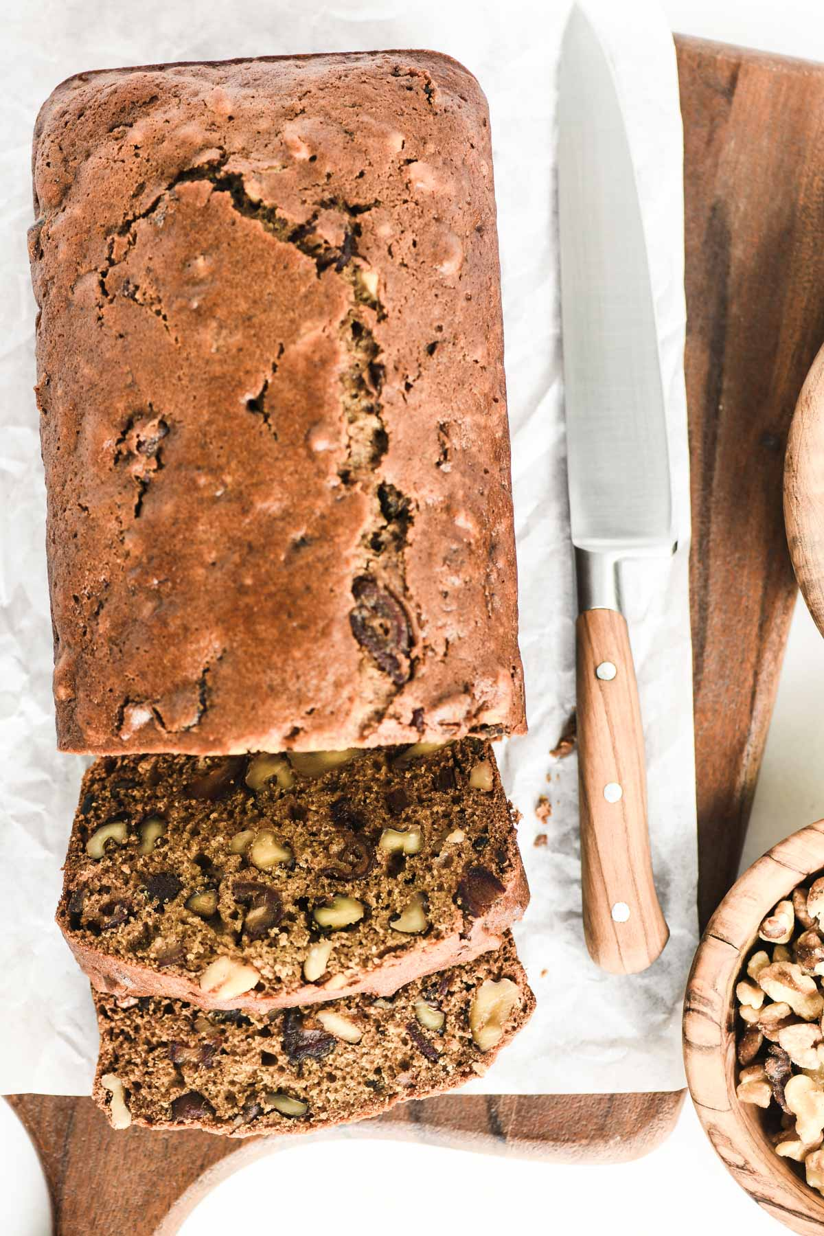 slicing a loaf of date nut bread