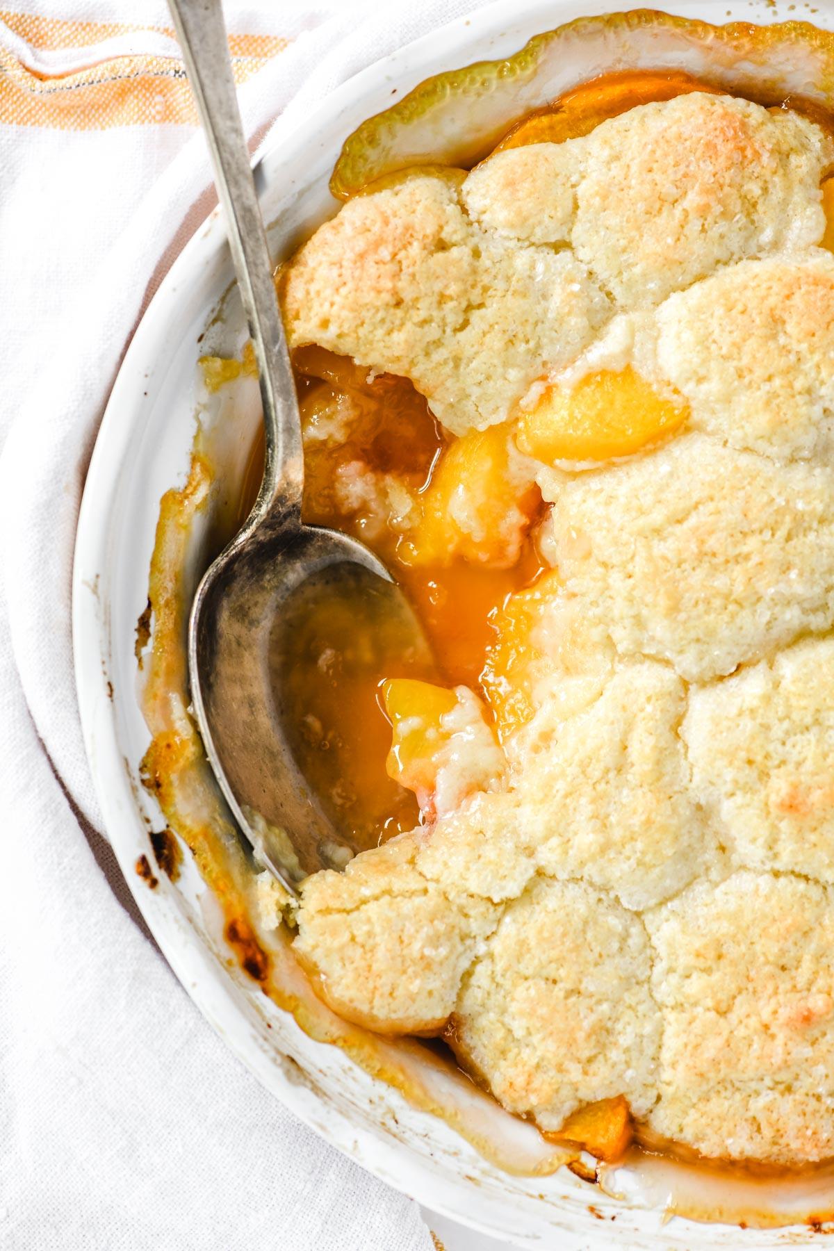 peach cobbler in a white pie plate