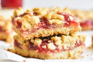 A stack of strawberry jam crumble bars.