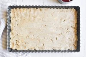 Pressing shortbread dough into tart pan.
