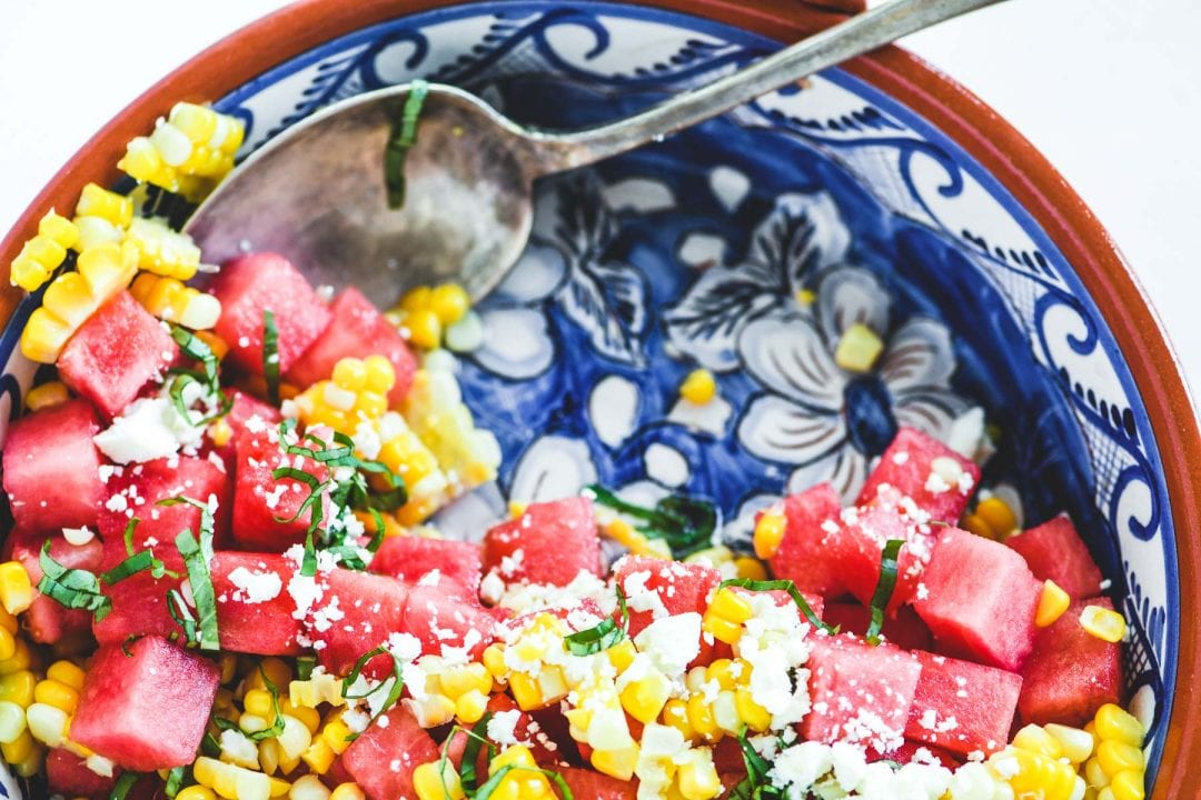 watermelon and corn salad in a blue dish