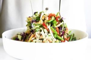 tossing Thai chicken salad