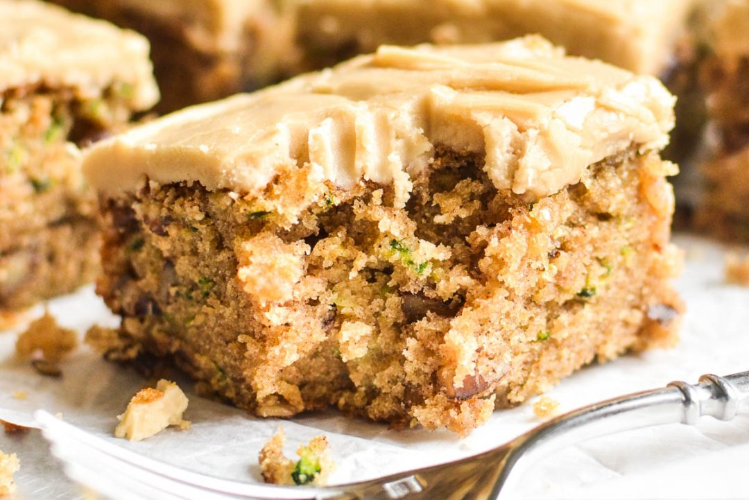A zucchini pecan bar with caramel frosting with a bite taken out.