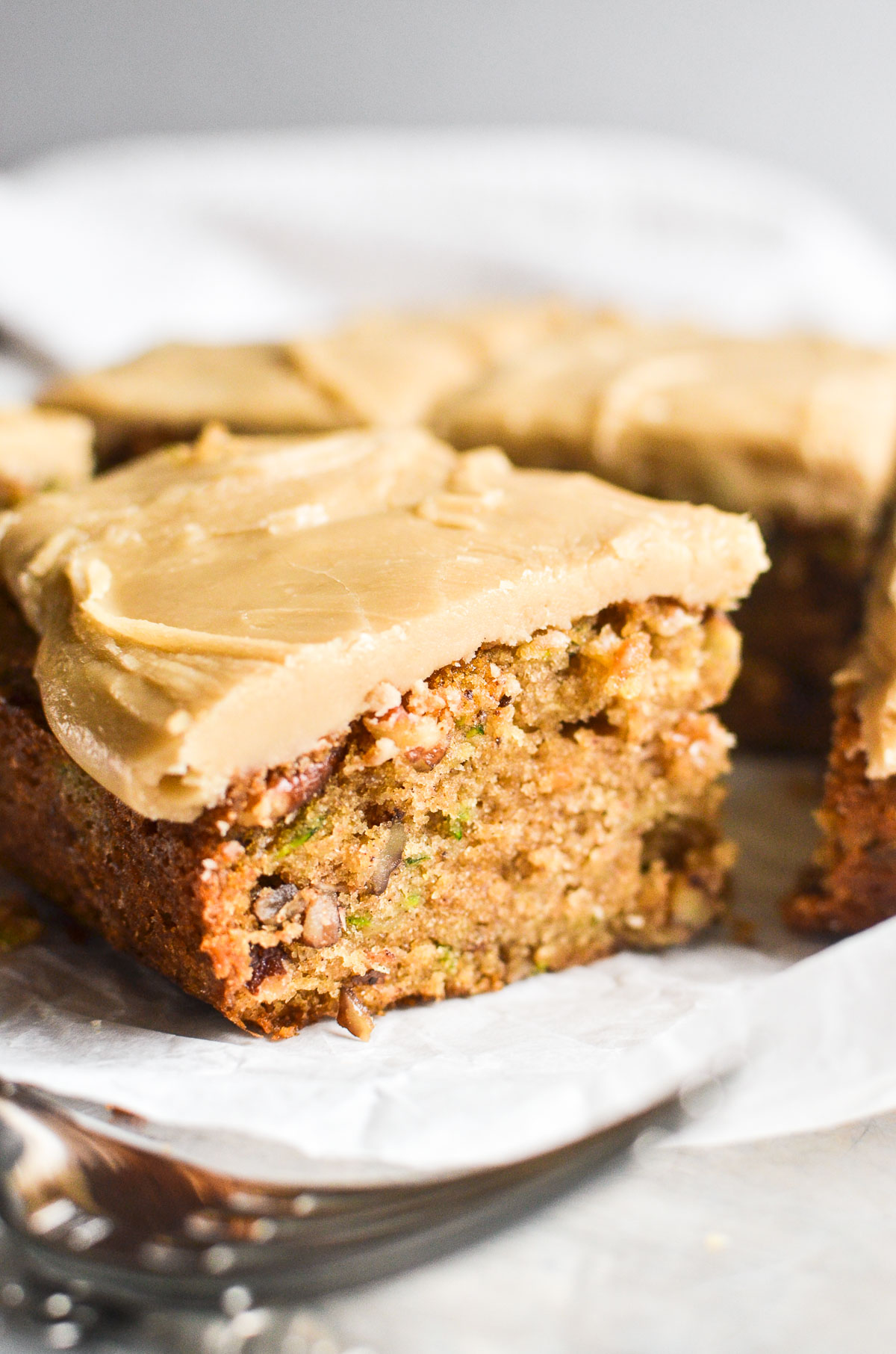 a zucchini bar topped with caramel frosting, with fork
