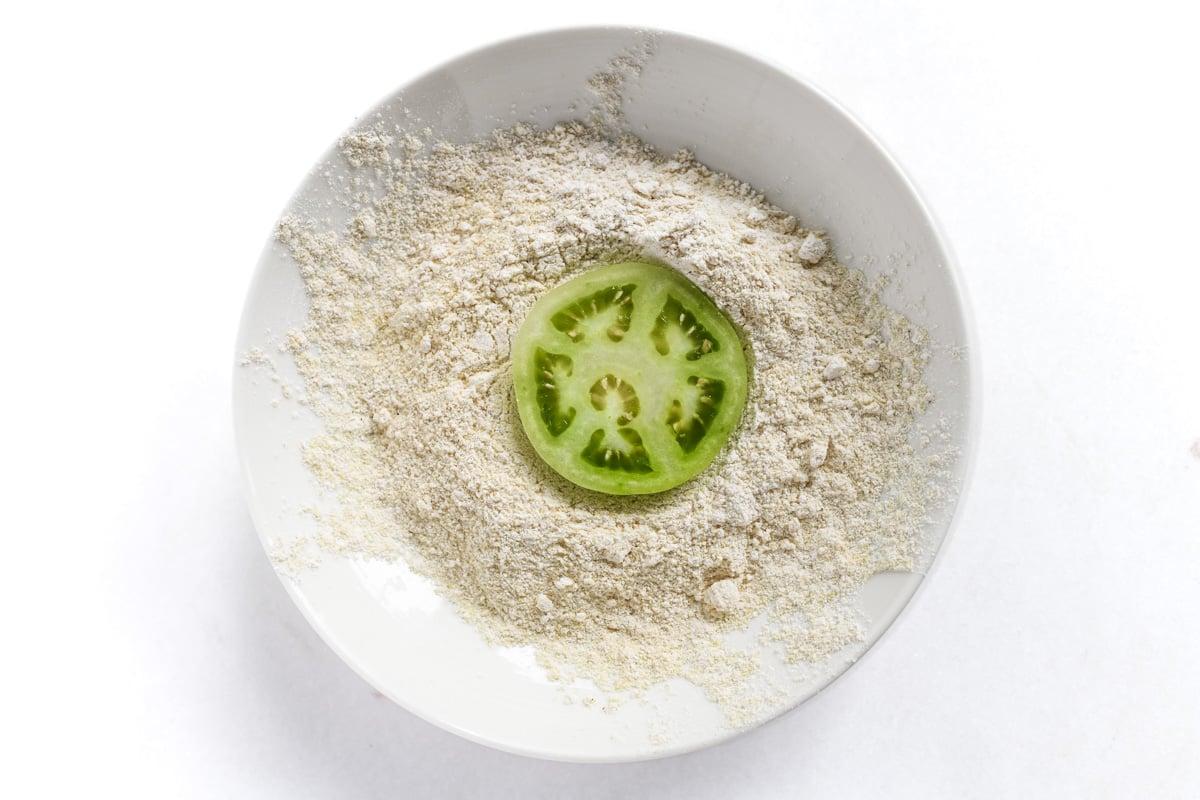 green tomato in cornmeal mixture