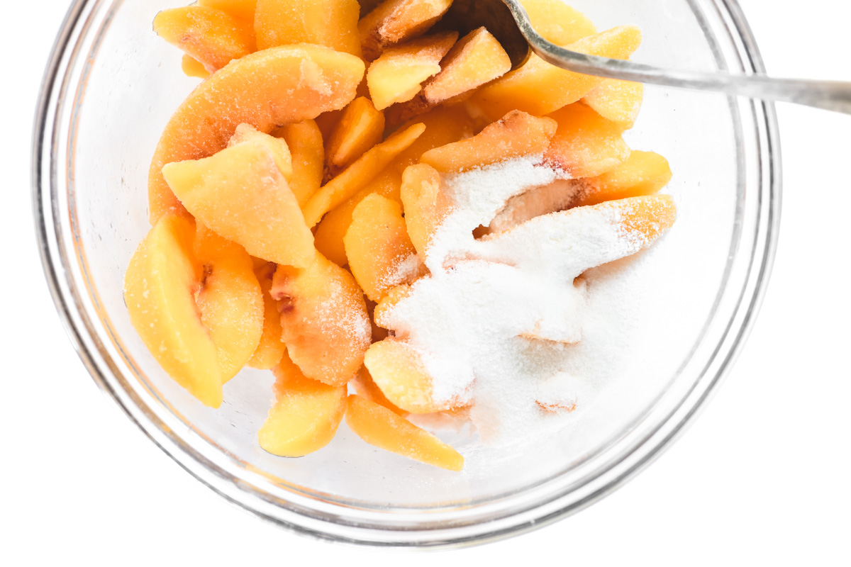 tossing peaches with sugar