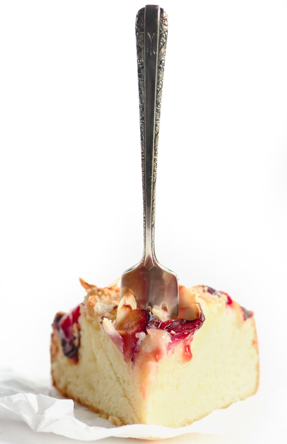 fork in a slice of ricotta plum cake
