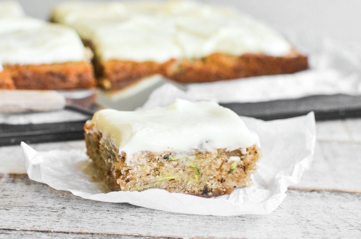 A slice of zucchini sheet cake on a piece of parchment paper.
