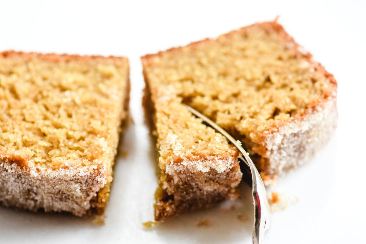 fork cutting into a slice of apple cider doughnut loaf cake