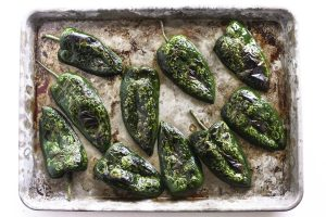blistered peppers on a baking sheet