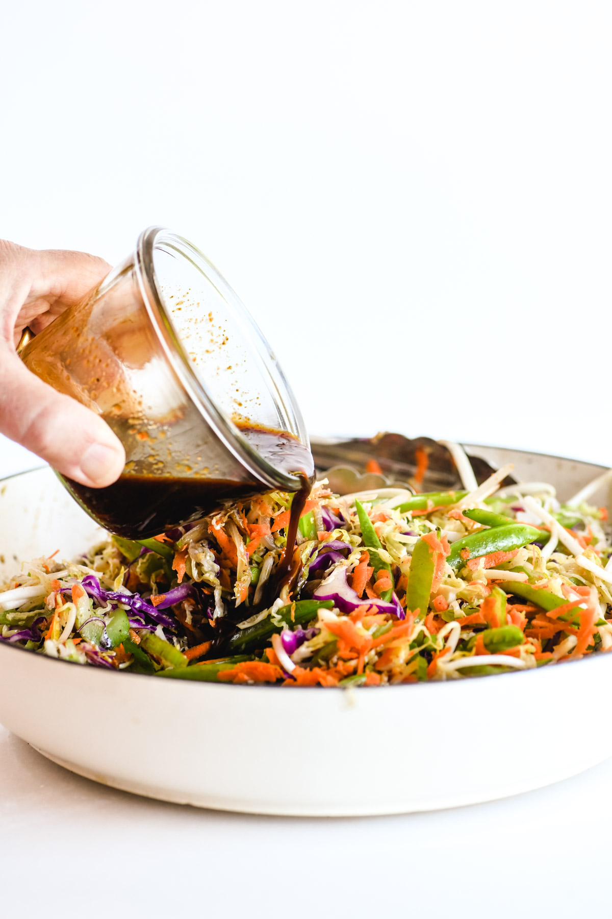 pouring sauce on egg roll bowl mixture