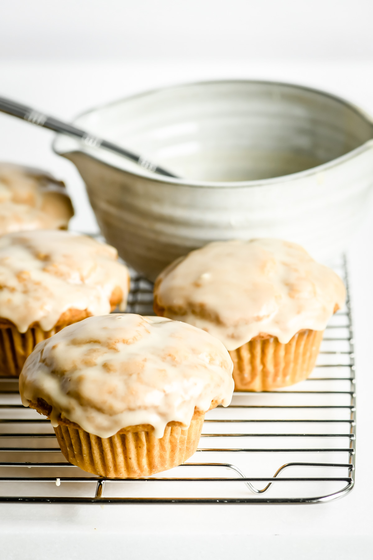 maple glazed pumpkin muffins on a rack with bowl