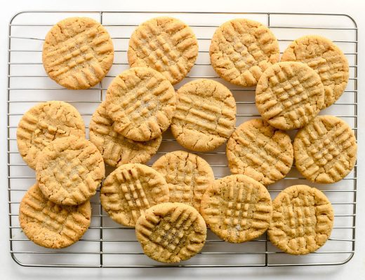 peanut butter cookies, piled on a baking rack