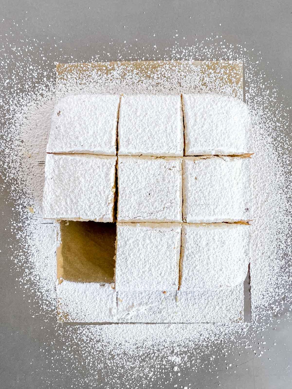 slicing a powdered sugar doughnut cake