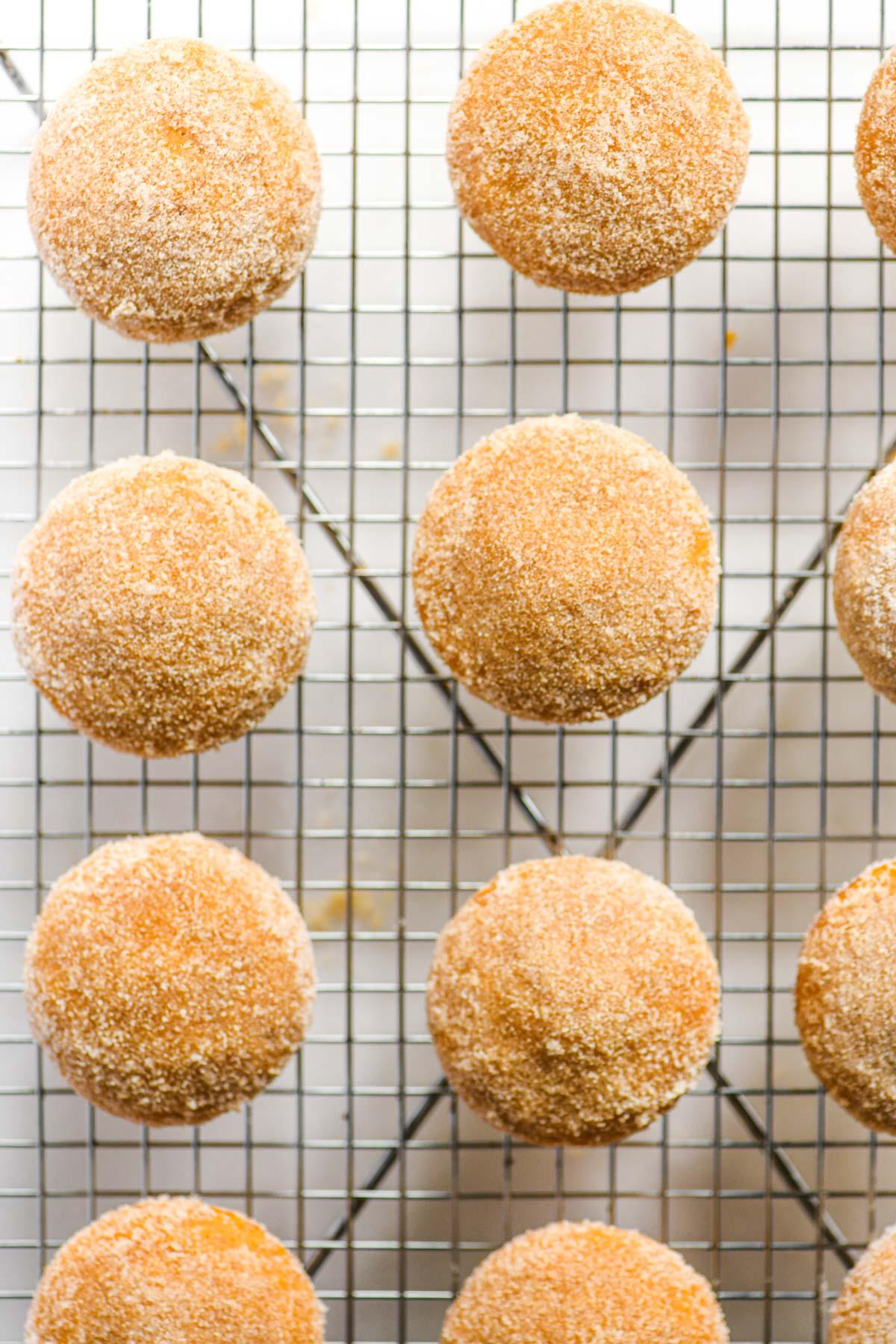 pumpkin doughnut muffins on a cooling rack, coated in sugar