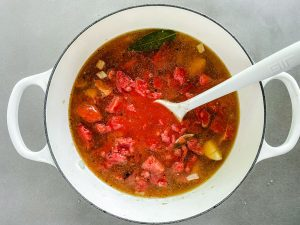 adding broth and tomatoes to soup pot