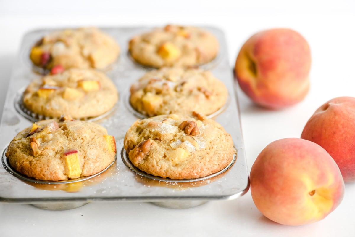 spiced peach muffins in a muffin tin