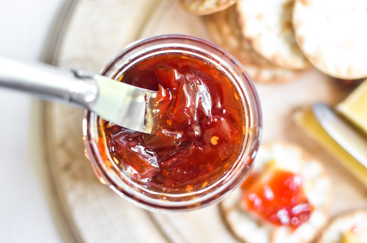 A jar of tomato jam with a small knife.