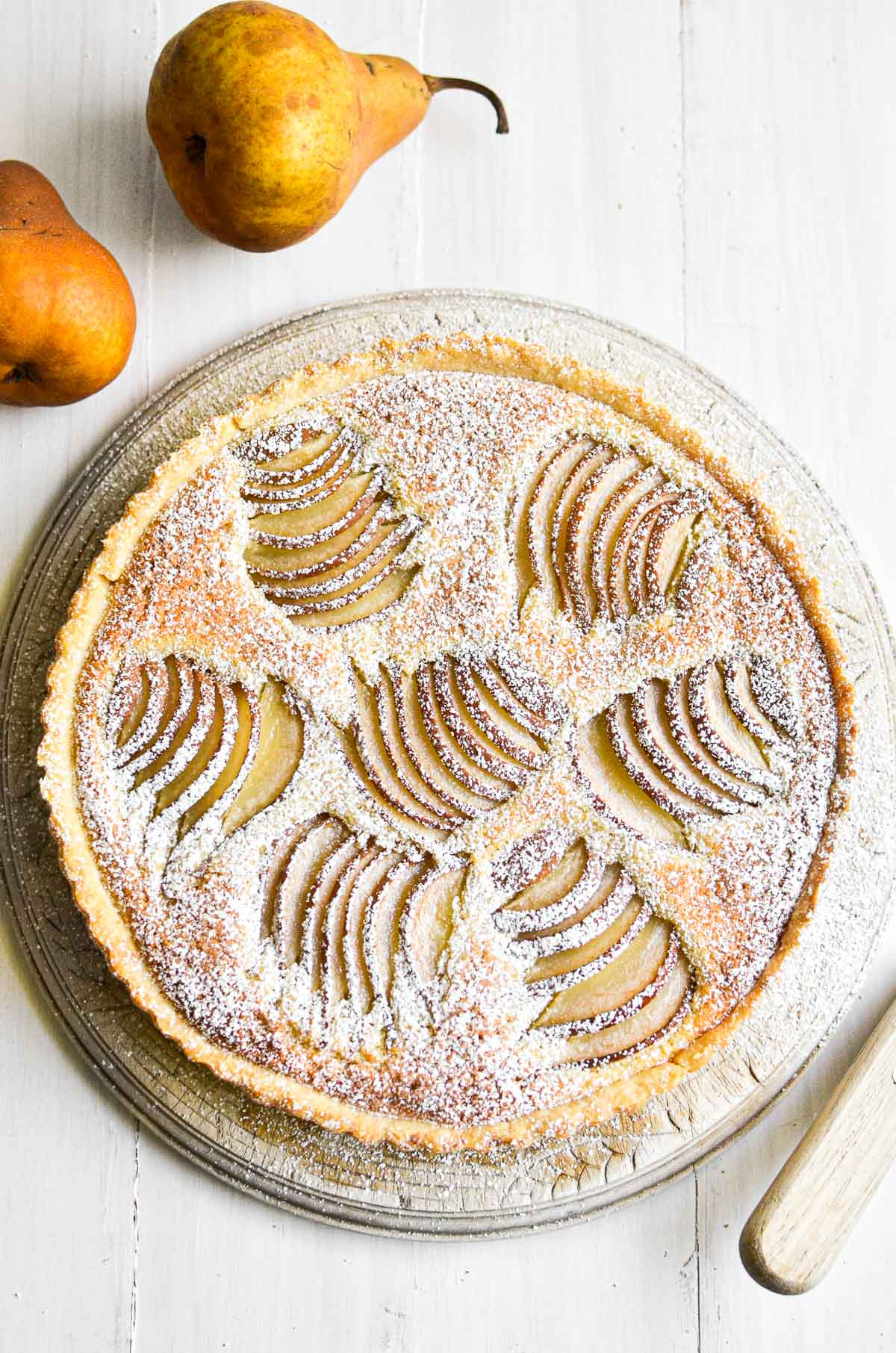 Pear and almond tart, dusted with powdered sugar.