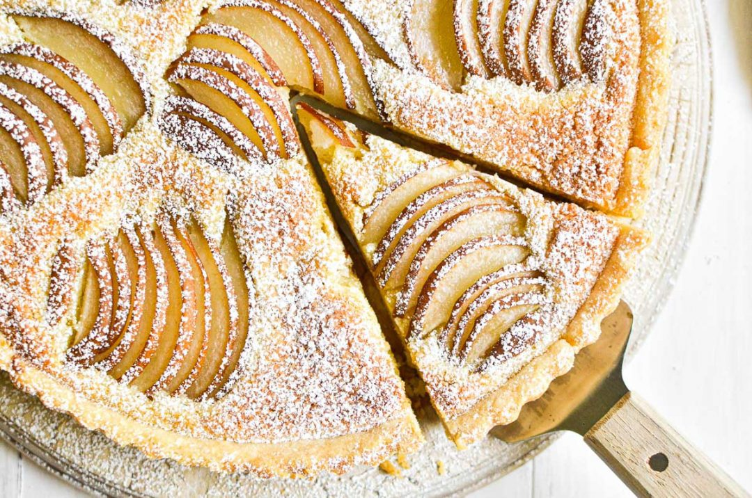 Pear and almond tart being sliced.