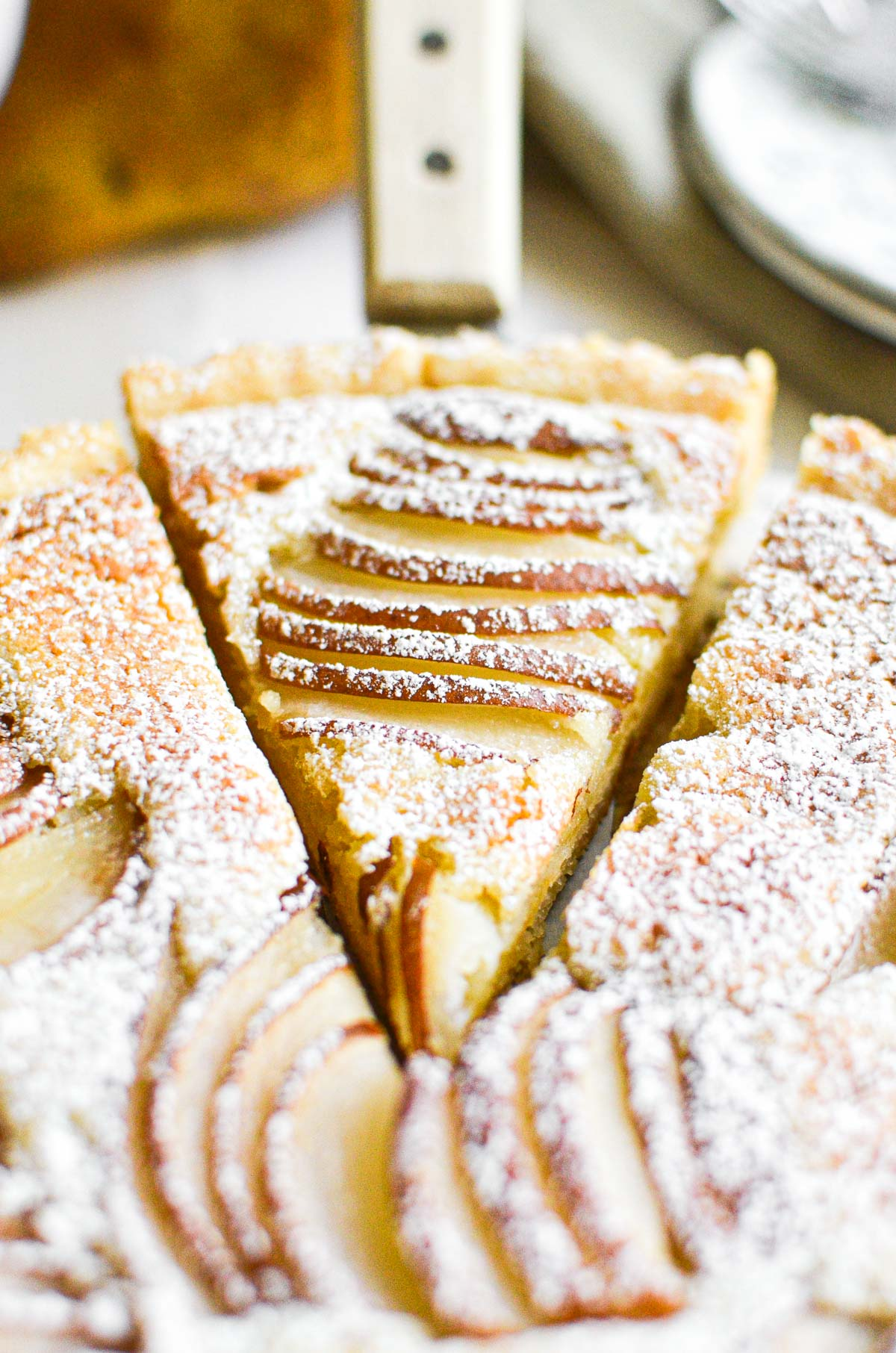 Close up of a slice of pear and almond tart.