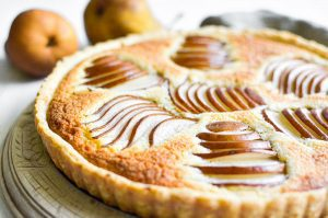 Pear and almond tart on a wooden cutting board.