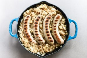 bratwurst on cabbage in a pan