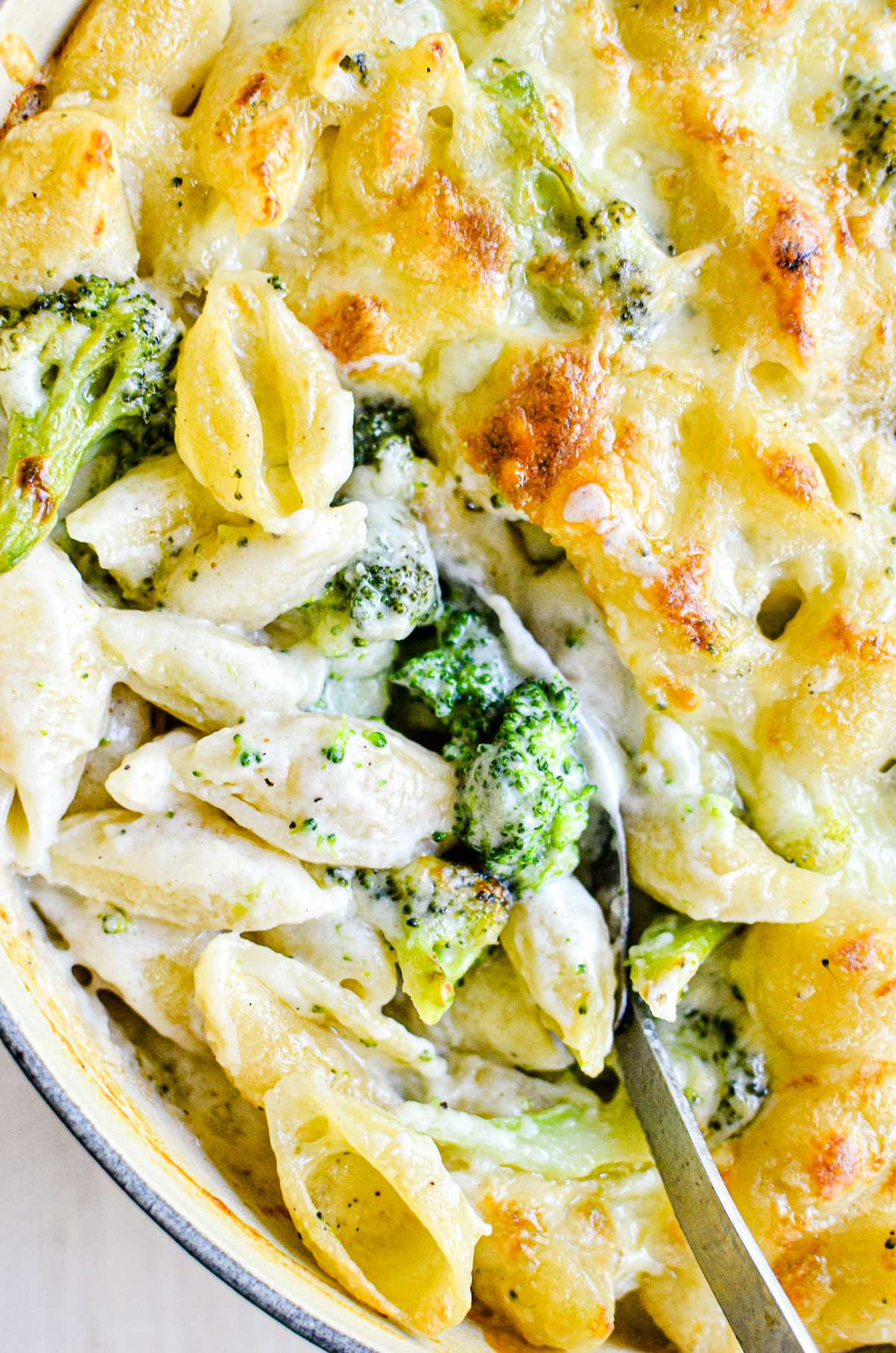 broccoli and cheddar baked shells, with spoon
