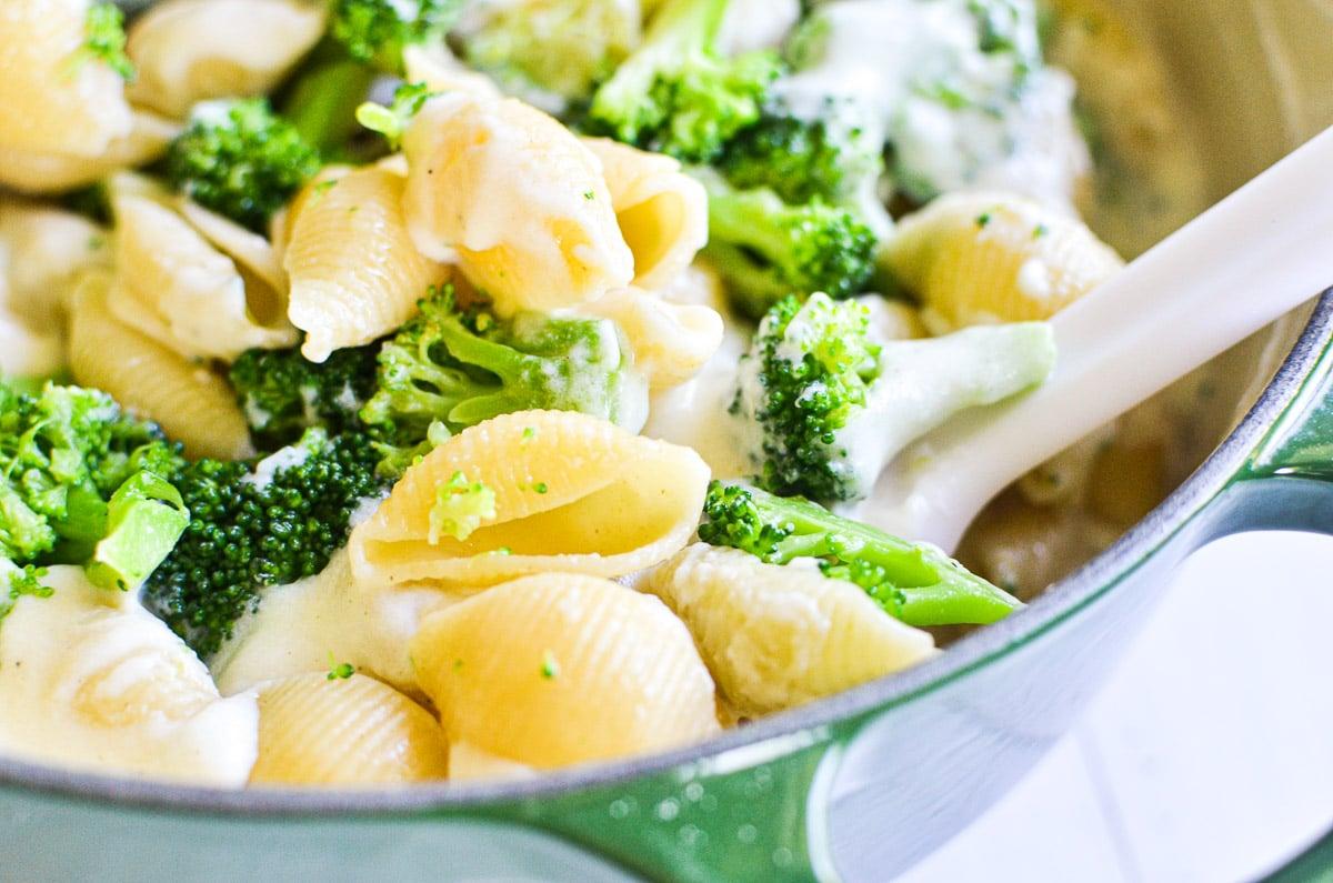 stirring broccoli cheddar shells in a green pot