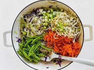 Adding veggies to pan for egg roll bowl