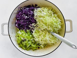 Adding cabbages and celery to pan