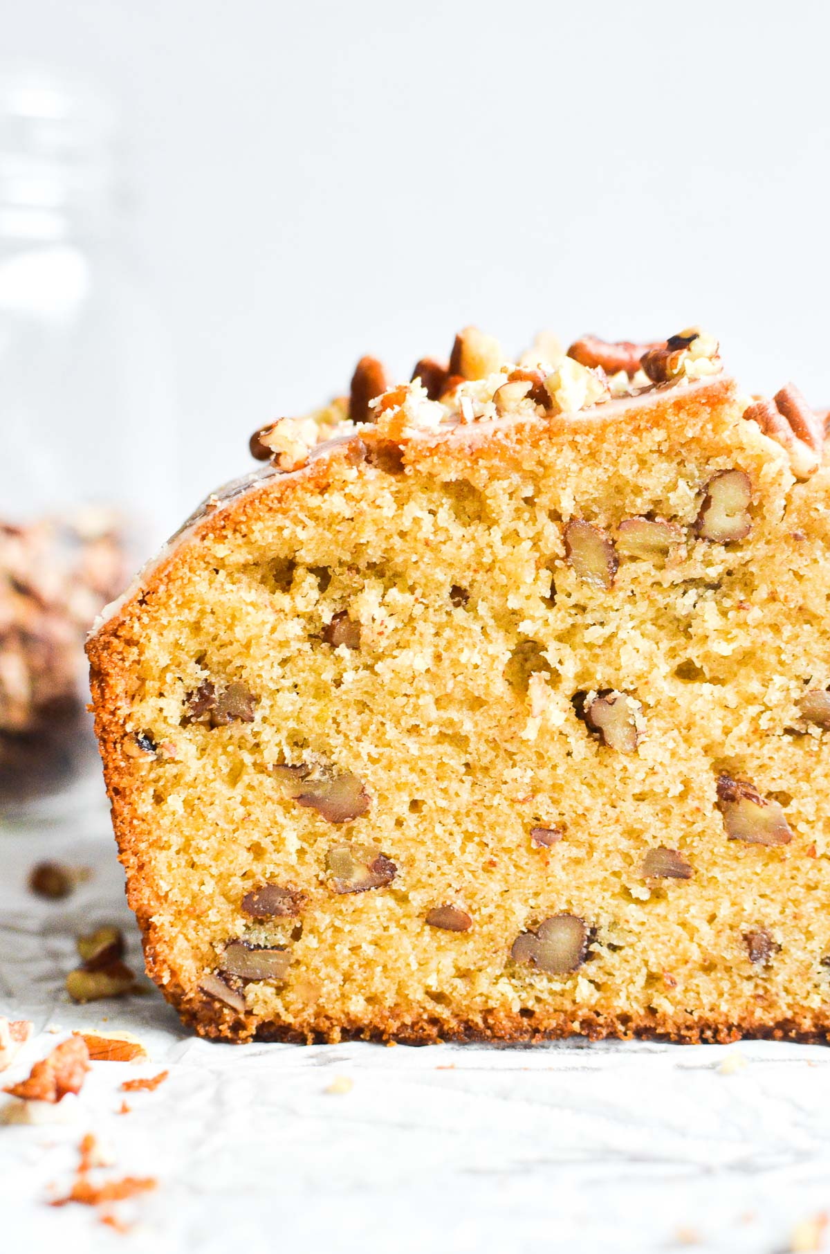 a slice of maple pecan pound cake on parchment paper