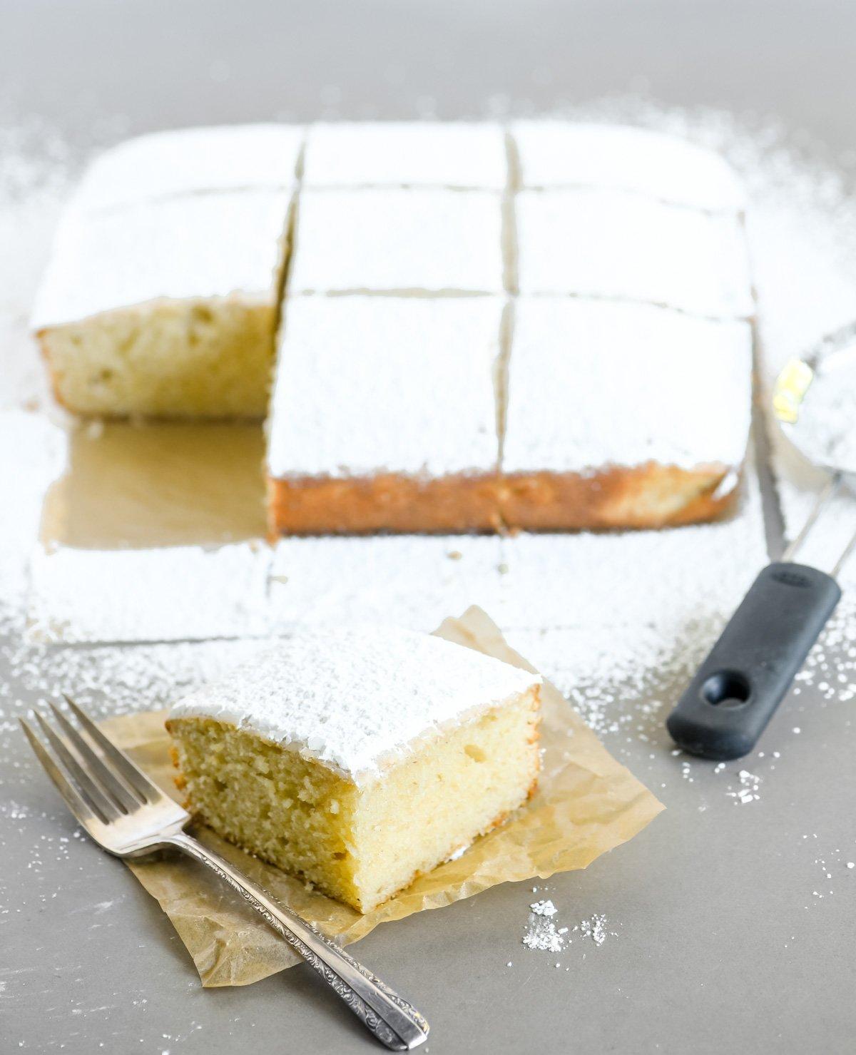 slicing a piece of powdered sugar doughnut cake