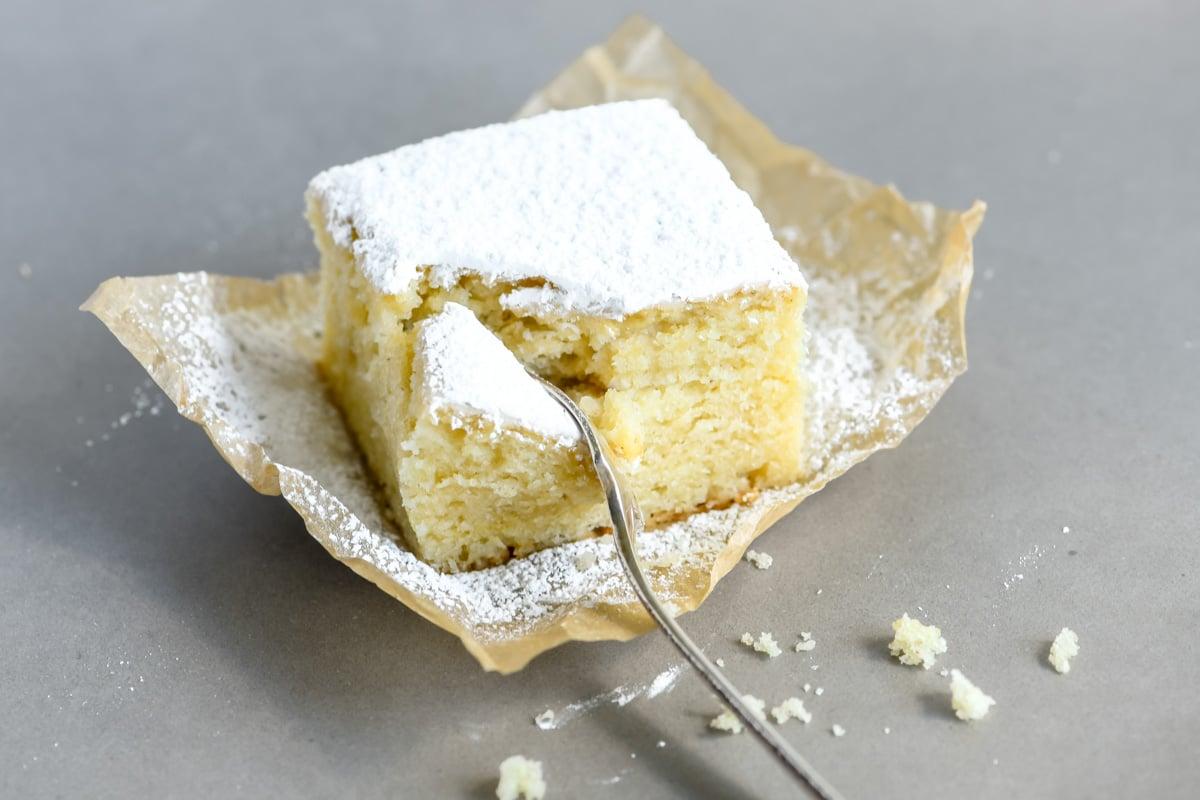 taking a bite of a powdered sugar doughnut cake