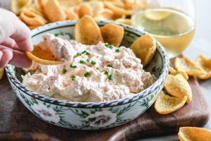 dipping a chip into smoked trout dip
