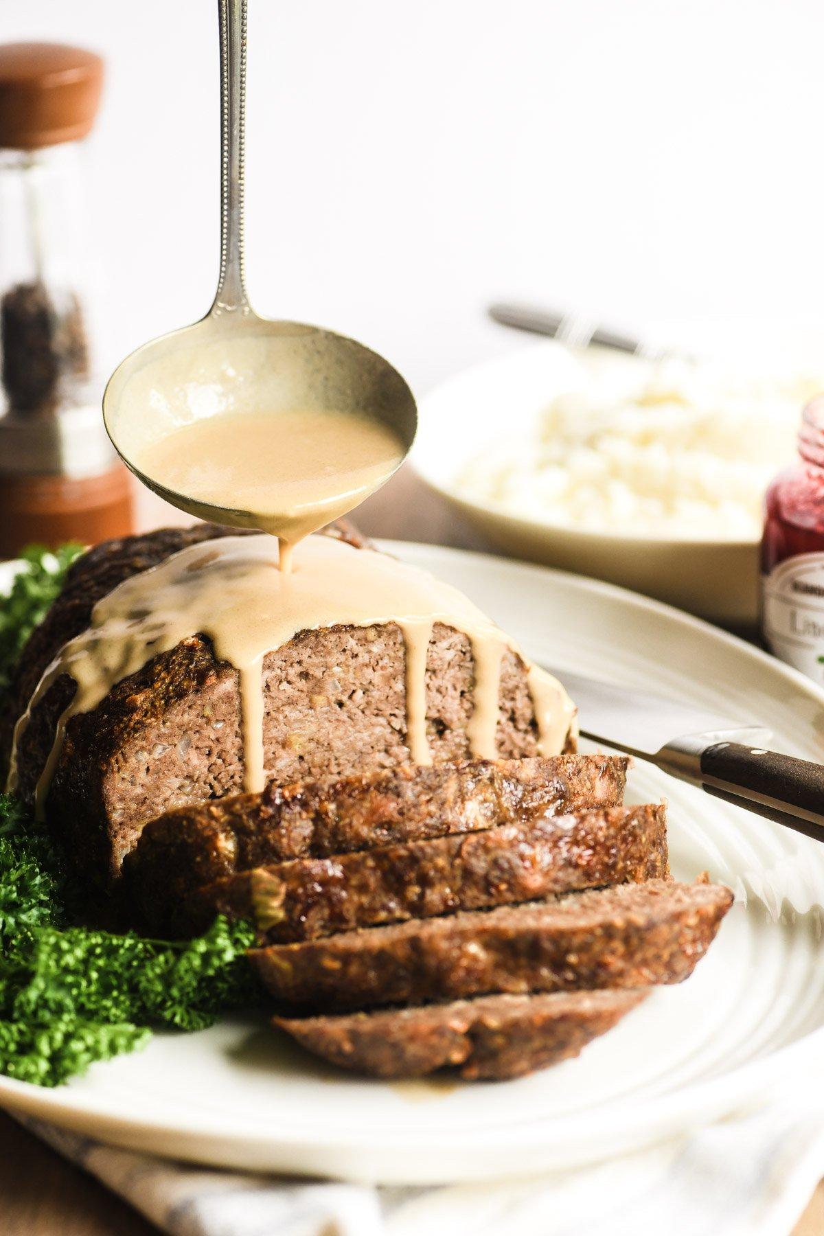 ladling gravy over Swedish Meatball Meatloaf