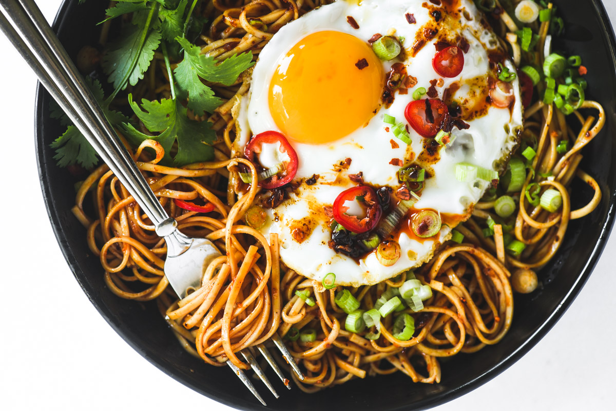 chili oil noodles in a black bowl with a fried egg