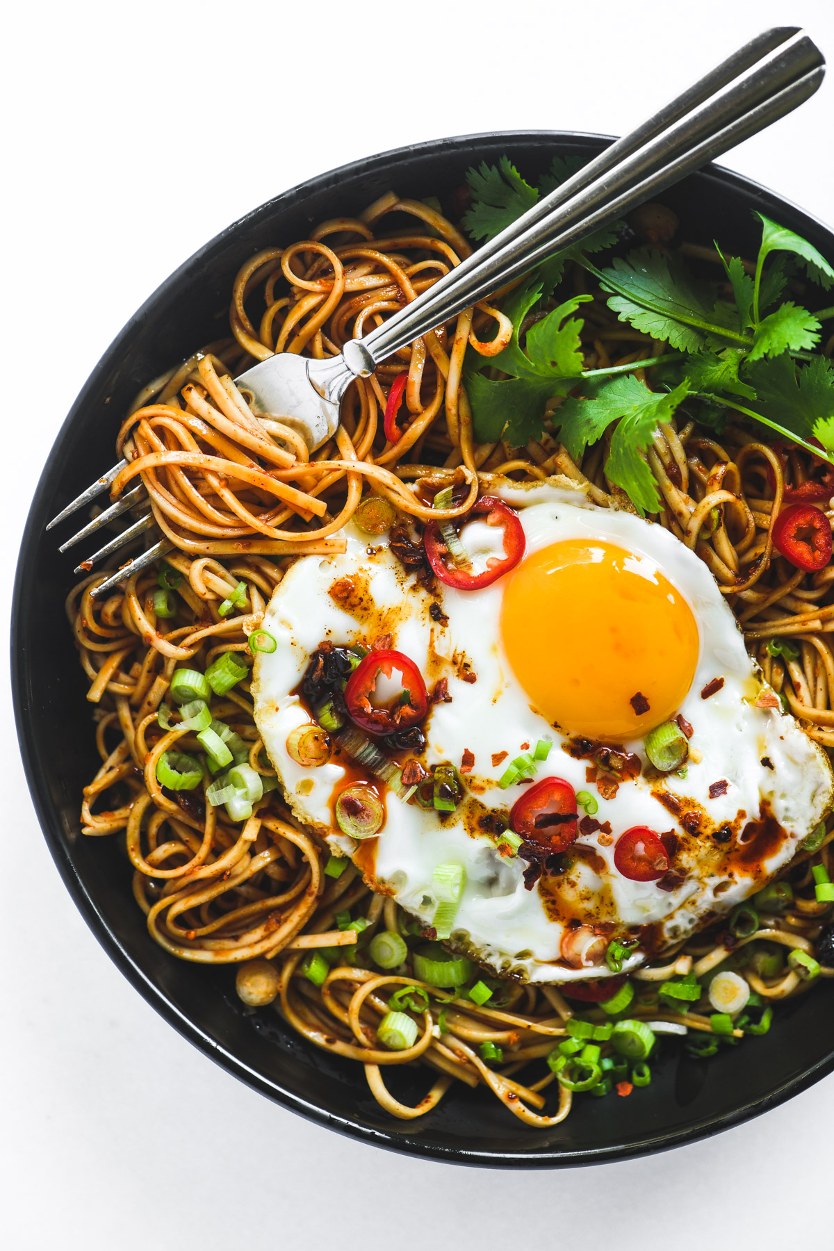 quick chili oil noodles in a black bowl with a fried egg