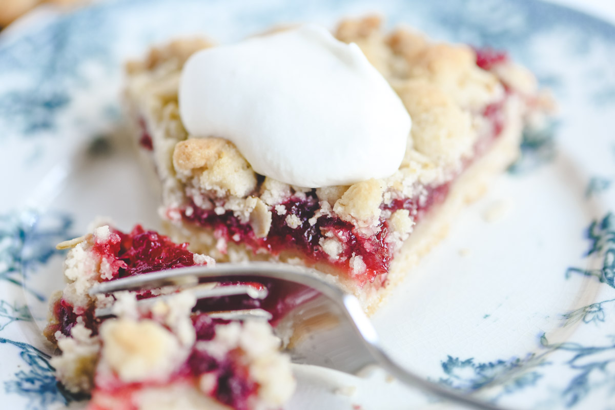 taking a bite of a lingonberry tart