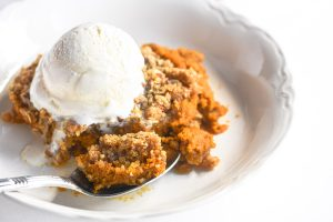 pumpkin crisp in a bowl with spoon
